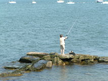 Boy Fishing. Young boy fishing in the ocean Stock Photo