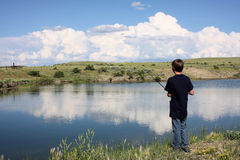 Boy Fishing. Young boy fishing at the edge of a pond with beautiful sky reflection in the water royalty free stock photos