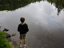 Boy Fishing. A boy fly fishing on a secluded mountain pond in the Green Mountains of Vermont royalty free stock image