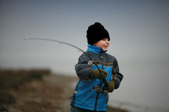 Boy Fishing. In winter by the ocean Royalty Free Stock Photos