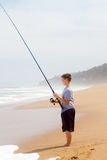 Boy fishing on beach Stock Photo