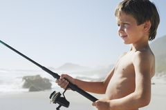 Boy Fishing On Beach Stock Photography