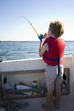 Boy fishing from a boat. Stock Images