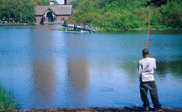Boy fishing in Central Park. Rear view of young black boy fishing on lake in Central Park, Manhattan, U.S.A Royalty Free Stock Images