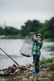 Boy fishing on the coast of river Royalty Free Stock Image