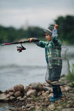 Boy fishing on the coast of river Stock Image