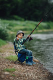 Boy fishing on the coast of river Stock Photo