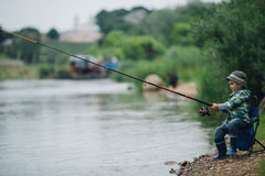 Boy fishing on the coast of river Royalty Free Stock Photo
