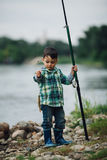 Boy fishing on the coast of river Stock Photography