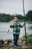 Boy fishing on the coast of river Royalty Free Stock Photography