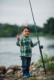 Boy fishing on the coast of river Stock Photos
