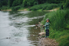 Boy fishing on the coast of river Royalty Free Stock Photos