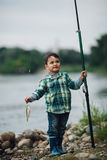 Boy fishing on the coast of river Stock Images