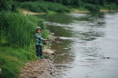 Boy fishing on the coast of river Royalty Free Stock Images
