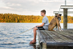 Boy Fishing with Dog on Dock at Lake Stock Photography