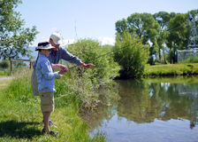 Boy Fishing with Grandpa. A grandfather teaches his grandson how to fly fish. Learning to fly fish on a children's trout pond in Montana Royalty Free Stock Photo