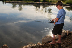 Boy fishing at a lake Royalty Free Stock Photos
