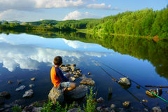 Boy fishing on the lake Royalty Free Stock Photos