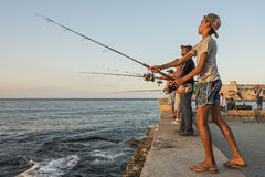 Boy fishing Malecon sunset Havana. Boy and a goup of men fishing at Malecon sunset in Havana, Cuba. Citizens of Havana is called Habaneros in Spanish Stock Photo