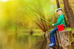 Boy fishing near beautiful pond with fishrod Stock Images