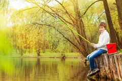 Boy fishing near the pond with green fishrod Stock Images