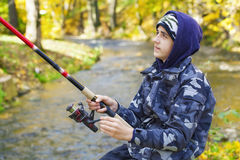 Boy fishing near river Stock Image