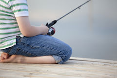 Boy fishing off dock in summer. A boy in jeans is fishing off a floating dock in the summer Royalty Free Stock Photo