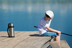 Boy fishing on the pier and looking for tea in a thermos. The boy looks at the tea thirsty Royalty Free Stock Photos