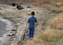 Boy with a Fishing Pole on the Shoreline. A boy carries his fishing pole along the shoreline of a lake Stock Photos