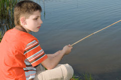 Boy fishing on the pond. A boy is fishing sitting at the country pond Stock Photo