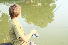 Boy fishing on pond. Small boy in green t-shirt fishing on pond with fish-rod Stock Image