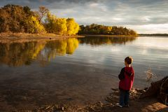 Boy fishing on Ray Roberts Lake, Texas. Late evening fall colors on the shore of Ray Roberts Lake with a young boy fishing. Calm, reflective water in a tranquil royalty free stock photography