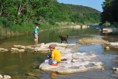 Boy Fishing in the River. Boy with his mother and family dog is fishing in a beautiful, rocky, Paluxy River near Cleburne, Texas Stock Images