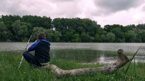 The boy is fishing. On the river bank stock footage