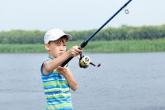 Boy fishing on river, summer Stock Image
