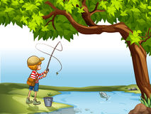 Boy fishing at the river Stock Photos