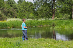 Boy with a fishing rod on the river bank Stock Image