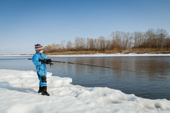 Boy fishing with rod on river in winter. Stock Photos