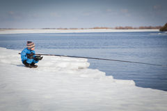 Boy fishing with rod on river in winter. Stock Images