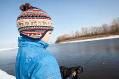 Boy fishing with rod on river in winter. Royalty Free Stock Photography