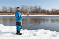 Boy fishing with rod on river in winter. Royalty Free Stock Image