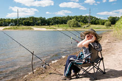 Boy with fishing rod sitting on the shore of the pond. Boy in big hat with fishing rods sitting on the shore of the pond, playing the binoculars Stock Photography
