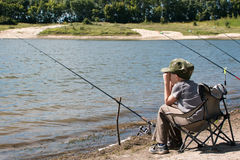 Boy with fishing rod sitting on the shore of the pond. Boy with fishing rod sitting on a chair on the shore of the pond and looks into the distance Stock Image