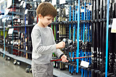 Boy with fishing rod in sport shop Royalty Free Stock Photo