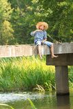 Boy fishing with rod at straw hat Royalty Free Stock Photo