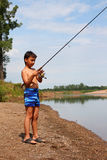 Boy fishing with spinning stock photography