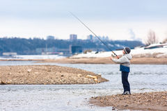 Boy fishing on spinning on the river Stock Image