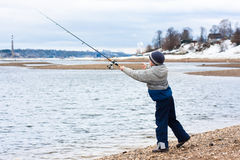 Boy fishing on spinning on the riverbank Royalty Free Stock Photos