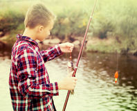Boy fishing using rod from water side Stock Image