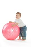 Boy with a fitness ball. A little boy with a big pink fitness ball Stock Photography